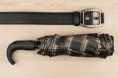伞和真皮皮带说谎木表面上 免版税图库摄影