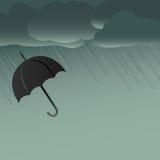 黑伞在与雨落的风雨如磐的天空下 库存照片
