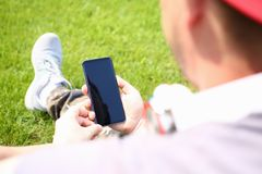 伟大现代手举行智能手机的公园 免版税库存照片