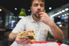 伟大的开胃三明治在一个年轻人的手上 人在餐馆哺养快餐 免版税库存图片