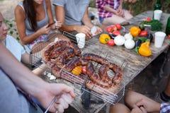 伟大的开胃香肠,烤 朋友吃油煎的香肠户外 与朋友的暑假 免版税库存图片