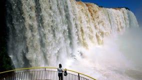 伟大的瀑布的背景的女孩,站立与被伸出的胳膊 股票录像