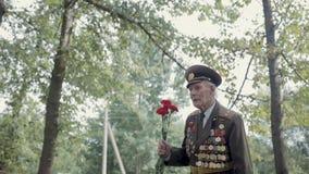 伟大的爱国战争和第二次世界大战的一个年长灰发的退伍军人在制服与许多徽章和顺序去 影视素材