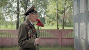伟大的爱国战争和第二次世界大战的一个年长灰发的退伍军人在制服与许多徽章和顺序站立 影视素材