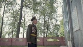 伟大的爱国战争和第二次世界大战的一个年长灰发的退伍军人在制服与许多徽章和顺序站立 股票视频