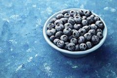 伟大的越桔或蓝莓在板材在蓝色土气背景 例证百合红色样式葡萄酒 免版税库存照片