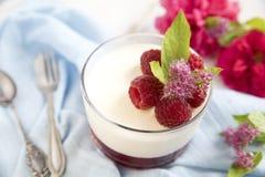 伟大的panacotta点心用莓,在一把蓝色背景和葡萄酒匙子和叉子 免版税库存照片