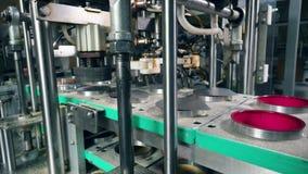 传动机在食物工厂投入在容器上的箔盖子 股票录像