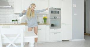 传神女孩跳舞在厨房里 库存图片