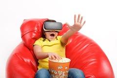 传神男孩用玉米花和VR风镜 库存图片