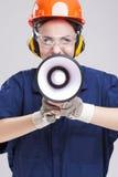 传神白种人女性画象有呼喊在安全帽的扩音器垫铁的 装备工作服 免版税库存图片