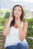 传神青少年的女孩谈话在手机户外在长凳 库存照片