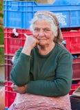 传统上加工好的老妇人农夫在卖她的produ的工作 免版税库存图片