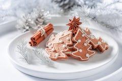 传统上圣诞节的姜饼曲奇饼在白色板材 免版税库存照片