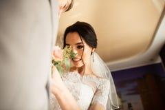 传统上,新娘在房子接触新郎的小花束 在手旁边的新郎花束在衣服 免版税库存图片