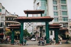 传统东方门和现代大厦在胡志明,越南街道上  免版税库存照片