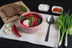传统乌克兰俄国罗宋汤用在碗的豆 红色甜菜根在黑桌上的汤罗宋汤板材  免版税图库摄影