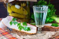 传统乌克兰和俄国开胃菜,当用餐时 食物,当喝酒精时 伏特加酒和三明治用烟肉、大蒜和p 免版税库存图片