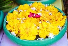 传统亚洲泰国建筑室内设计:有开花的兰花、万寿菊和茉莉花的装饰的陶瓷瓷碗 图库摄影