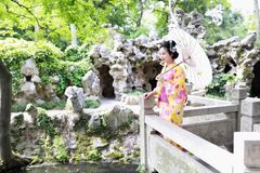 传统亚裔日本在一个graden立场的妇女艺妓佩带的和服戏剧在桥梁举行一把白色伞 免版税库存照片