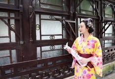 传统亚裔日本妇女新娘艺妓佩带的和服戏剧在graden举行伞支持小船 免版税库存图片