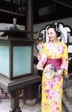 传统亚裔日本妇女新娘艺妓佩带的和服戏剧在graden举行爱好者 免版税库存图片