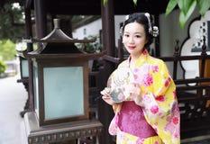 传统亚裔日本妇女新娘艺妓佩带的和服戏剧在graden举行爱好者 免版税图库摄影