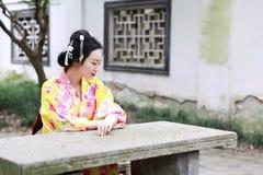 传统亚裔日本美丽的在室外春天庭院里女服和服坐石长凳 库存照片