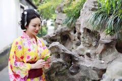 传统亚裔日本美丽的在春天庭院公园女服和服支持竹子享受业余时间 免版税库存照片