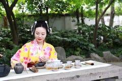 传统亚裔日本美丽的女服和服展示茶艺术,并且仪式坐石长凳在室外春天庭院里 库存图片