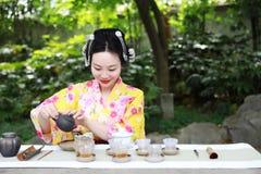 传统亚裔日本美丽的女服和服展示茶艺术,并且仪式坐石长凳在室外春天庭院里 图库摄影