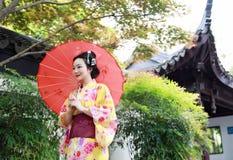 传统亚裔日本美丽的妇女新娘在室外春天庭院里穿有红色伞的和服在一个寺庙前面 免版税图库摄影