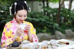 传统亚裔日本美丽的艺妓在夏天春天outdorr庭院里女服和服展示茶艺术仪式饮料茶 免版税库存照片