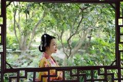 传统亚裔日本美丽的艺妓在手边女服有一个爱好者的和服在夏天自然 免版税图库摄影