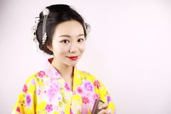 传统亚裔日本美丽的艺妓女服和服微笑并且在手边拿着一个爱好者在白色背景 库存照片