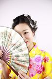 传统亚裔日本美丽的艺妓女服和服微笑并且在手边拿着一个爱好者在白色背景 图库摄影