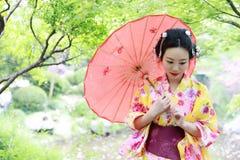 传统亚裔日本美丽的艺妓女服有一把红色伞的和服新娘在graden 免版税库存照片