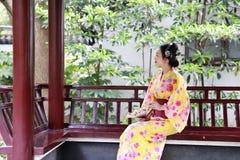 传统亚裔日本美丽的艺妓妇女新娘佩带爱好者坐夏天自然的一个亭子的和服举行 免版税库存图片