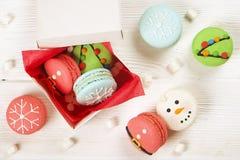 传统以雪人、雪花、圣诞树和圣诞老人` s腹部的形式圣诞节主题的法国蛋白杏仁饼干甜点有罐头的 免版税图库摄影