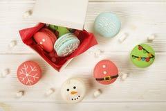 传统以雪人、雪花、圣诞树和圣诞老人` s腹部的形式圣诞节主题的法国蛋白杏仁饼干甜点有罐头的 库存照片
