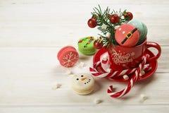 传统以雪人、雪花、圣诞树和圣诞老人` s腹部的形式圣诞节主题的法国蛋白杏仁饼干甜点有罐头的 免版税库存照片