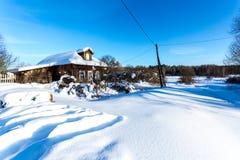 传统俄国村庄在多雪的霜冬天 免版税库存图片