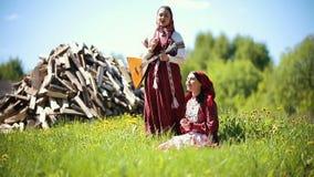 传统俄国衣裳的两年轻女人唱歌曲的由在firewoods背景的俄式三弦琴  股票录像