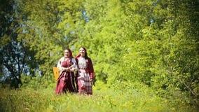传统俄国衣裳的两年轻女人走在领域和唱歌曲-拿着俄式三弦琴的他们中的一个的 股票录像