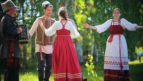 传统俄国衣裳的人们在握手的领域跳舞-他们中的一个播放手风琴音乐 影视素材