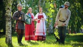 传统俄国衣裳的人们在领域跳舞-他们中的一个播放手风琴音乐 股票录像