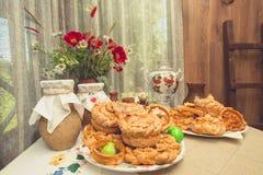 传统俄语被烘烤的物品 一张桌在一个土气房子里,有板材用小圆面包、饼和椒盐脆饼,俄国式茶炊, cla 库存照片