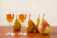 传统保加利亚家庭做的果子白兰地酒krushova rakia两块玻璃和在一张木桌上的四个梨反对轻的灰棕色 免版税库存照片