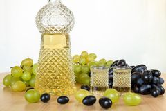 传统保加利亚家庭做的白兰地酒磁带果汁饮料,称grozdova葡萄rakia,在水晶瓶和两块玻璃中在向求爱 库存照片