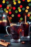 传统冬天仔细考虑了在葡萄酒玻璃和圣诞节装饰品的酒在光背景,选择聚焦并且定了调子图象 图库摄影
